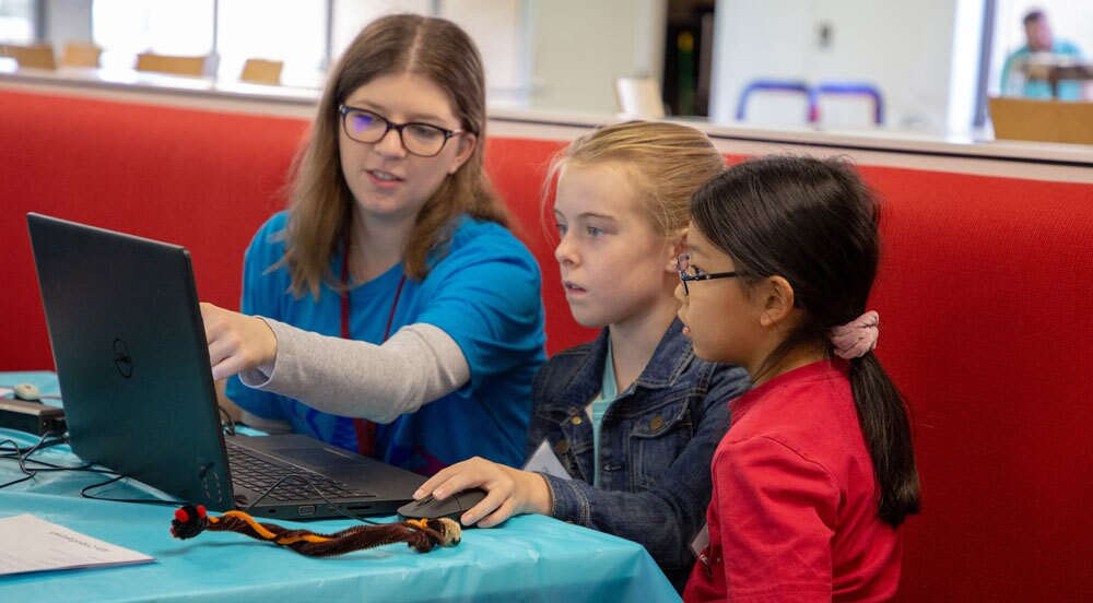 A VEX robotics teacher instruction two young students.