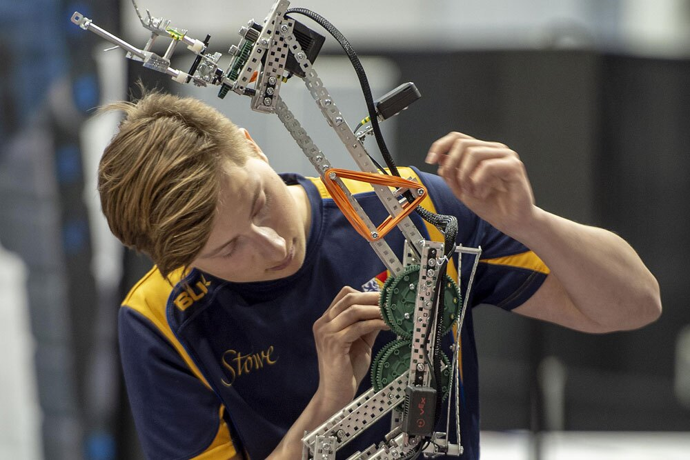 A young male robotics student adjusting his robot.