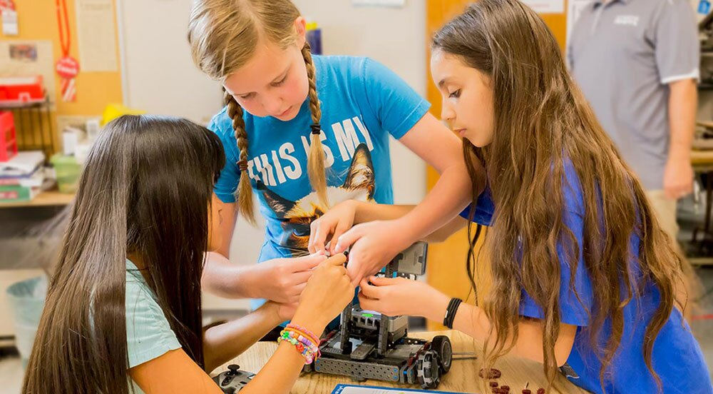 Three young girls building a VEX EDR robot.