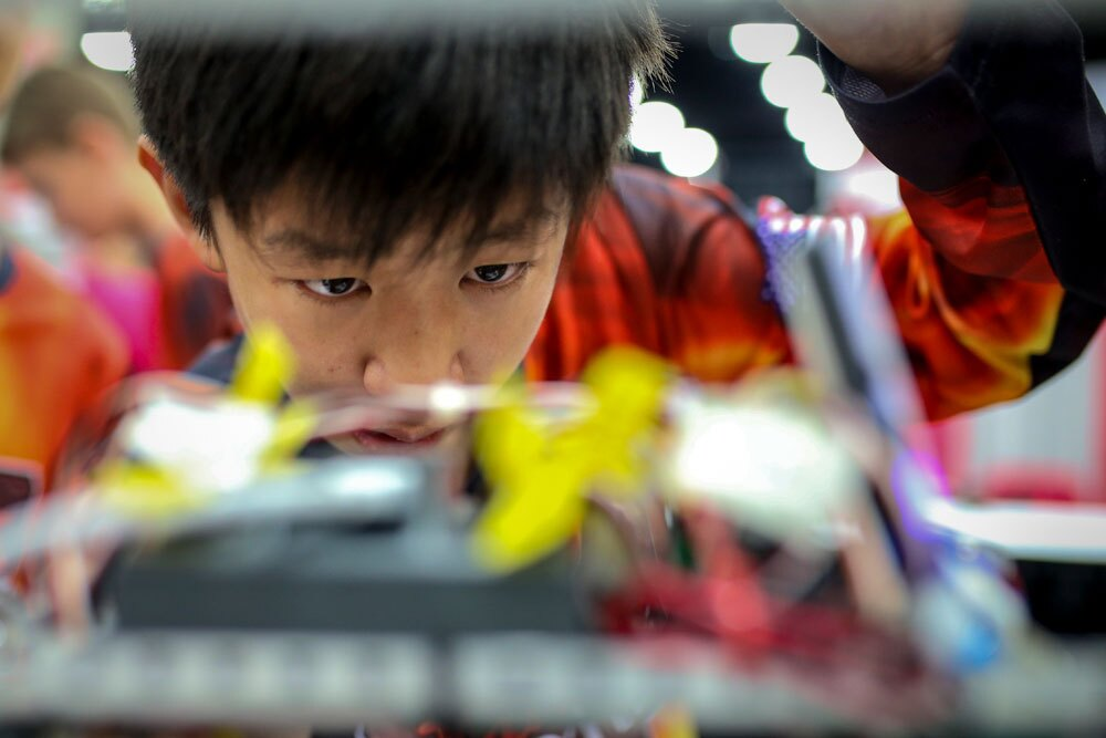 A young male student looking inside his robot.